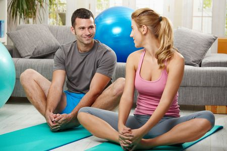 Young couple warming up before training, sitting on fitness mat, looking at each other smiling.