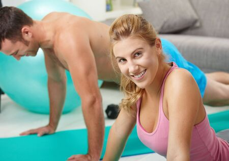 Young couple doing push up exercise at home in living room. photo