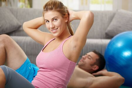 Young couple doing abdominal crunch lying on fitness mat at home in living room. Stock Photo - 6437917