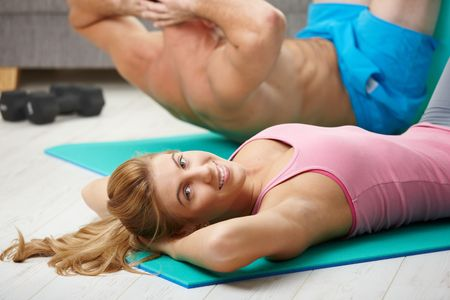crunch: Young couple doing abdominal crunch using fit ball at home.