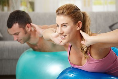 Young couple doing fit ball exercises in living room, smiling. Stock Photo - 6437806