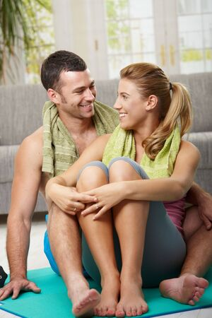 Happy couple resting after training, sitting on fitness mat in living room, looking at each other smiling. photo