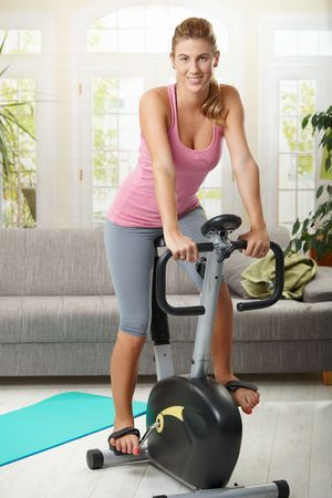 stationary bike: Young woman training on exercise bike at home, smiling. Stock Photo