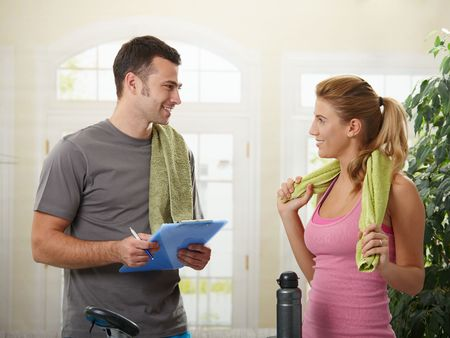 home gym: Young woman talking with her personal trainer at home.