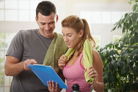 fitness trainer: Young woman checking training plan with her personal trainer at home.