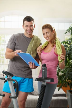 home trainer: Young woman checking training plan with her personal trainer standing beside exercise bike at home.