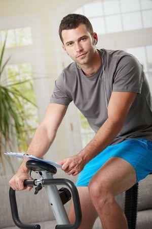 stationary bike: Man training on exercise bike at home, listening music.