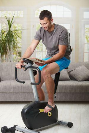 Equipaggi la seduta sulla bici fissa a casa, leggendo il giornale e ascoltando la musica.
