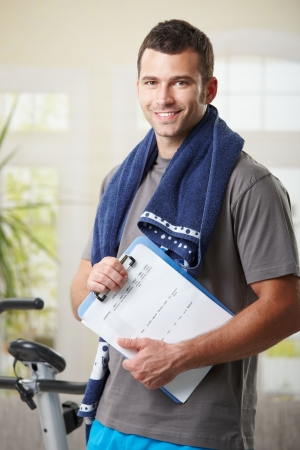 fitness trainer: Handsome personal trainer with training plan. Stock Photo