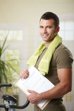 home trainer: Man wearing sportswear standing in living room at home, holding training plan.