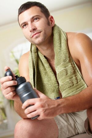 Tired man resting after training, holding bottle in hand. Stock Photo - 6437950