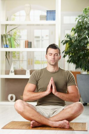 Man doing yoga exercise at home, sitting on floor in living room. Stock Photo - 6438004