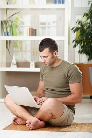 chat room: Casual man using laptop computer at home sitting on floor in living room. Stock Photo