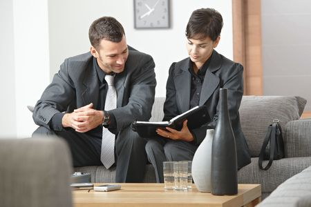 work      wear: Young business people having meeting at office sitting on sofa working in team.