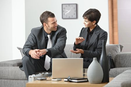 Young business people having meeting at office sitting on sofa businesswoman explaning to businessman. photo