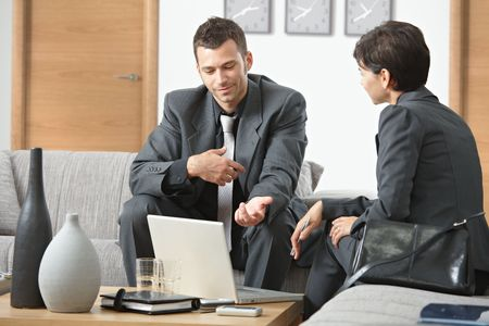 Young businessman explaining to businesswoman at office sitting on sofa talking, looking at laptop computer. Stock Photo - 6437993