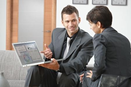 economia aziendale: Sorridente giovane imprenditore presenta sul computer portatile, seduta sul divano in ufficio.