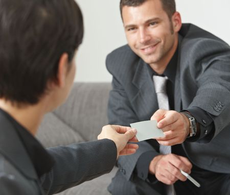 cooperating: Business meeting at office lobby, people sitting on sofa changing business cards. Focus on card. Stock Photo