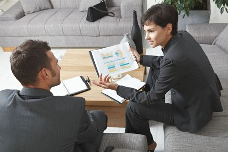 financial problems: Business meeting at office. Youing businsspeople sitting on sofa, talking over financial charts. Overhead view. Stock Photo
