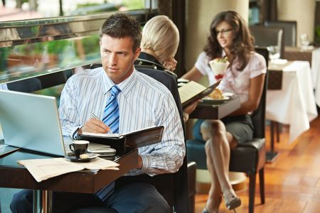 portable: Businessman sitting at table in cafe using laptop computer, writing notes. Young women having sweets in the background.