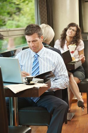 Businessman sitting at table in cafe using laptop computer, writing notes. Young women ordering sweets in the background. photo