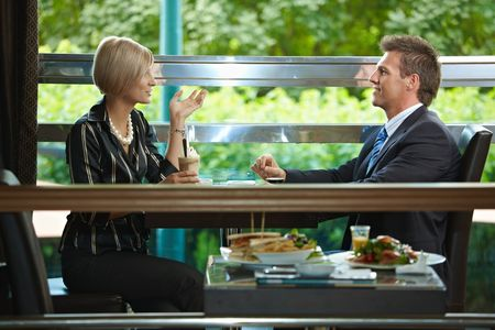 attire: Young businessman and businesswoman having a meeting in cafe. Stock Photo