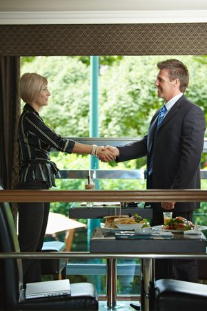 Young businessman and businesswoman shaking hands during a meeting in cafe. photo