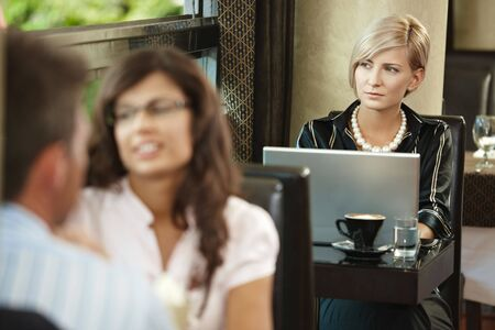 Young woman sitting at table in cafe, using laptop computer. photo