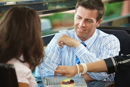 Young businessman and businesswoman talking in cafe. photo