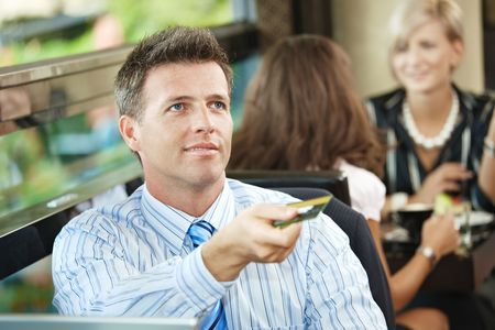 Closeup portrait of businessman sitting at coffe table in cafe, paying with credit card, smiling. Stock Photo