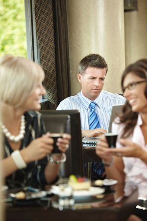 Businessman using laptop in cafe, young woman drinking coffee and talking in the foreground. Selective focus on businessman. photo