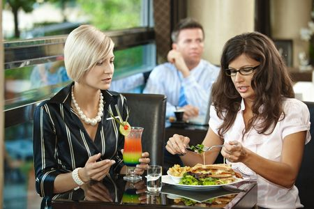 Young women sitting at table, eating sandwich and drinking cocktail in restaurant. photo