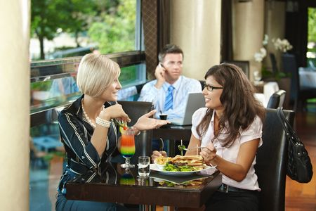 Young women sitting at table in cafe, eating sandwich and drinking cocktail, talking. Stock Photo - 6437990