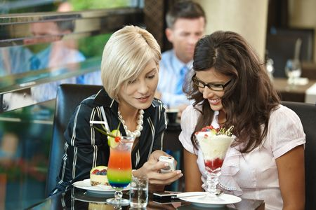 Young women sitting in cafe having sweets, looking at mobile phone. photo