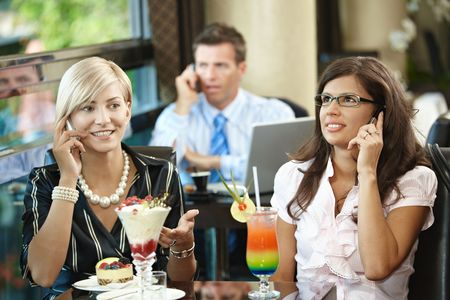 Young women sitting in cafe having sweets, talking on mobile phone. Stock Photo - 6437991