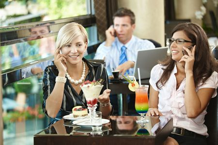 Young women sitting in cafe having sweets, talking on mobile phone. photo