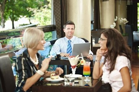 Businessman using laptop in cafe, young woman eating sweets and talking in the foreground. Selective focus on businessman. photo