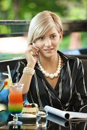 blond brown: Young businesswoman sitting at table in cafe, talking on mobile phone, reading magazine.