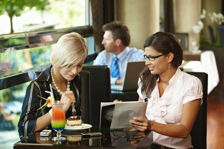 Young women sitting in cafe having sweets, looking at magazine. Stock Photo - 6437912