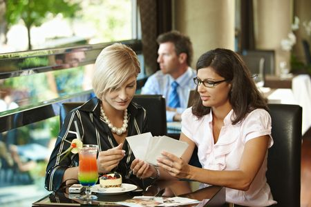 Young women sitting in cafe having sweets, watching photos, smiling. photo