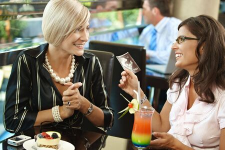 sonogram: Happy young women sitting in cafe having sweets, looking at sonogram, smiling.