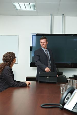 Happy businessman arriving to meeting room, smiling. Stock Photo - 6437554