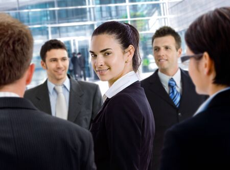officetower: Young businesswoman standing among other businesspeople, in front of office building.