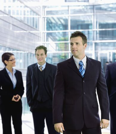 Young businessman standing in front of other businesspeople, out of office building. Stock Photo - 6438067
