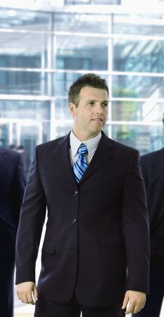 officetower: Portrait of young businessman standing in front of office building.