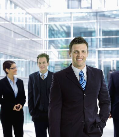 officetower: Happy businessman standing in front of other businesspeople, out of office building, smiling.