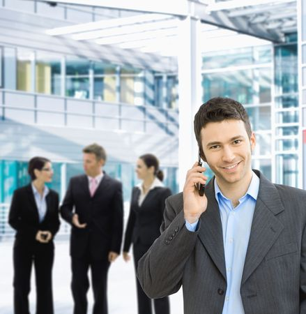 open collar: Portrait of happy businessman talking on mobile in office lounge. Stock Photo