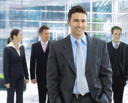 formalwear: Portrait of happy businessman standing in office lounge smiling.