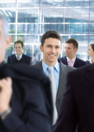 Young businessman walking in crowd in office lobby, smiling. Stock Photo - 6438318