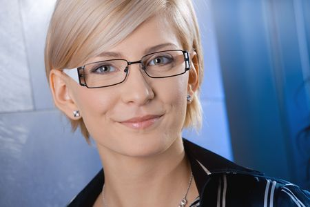 Closeup portrait of attractive young businesswoman wearing glasses, smiling. photo